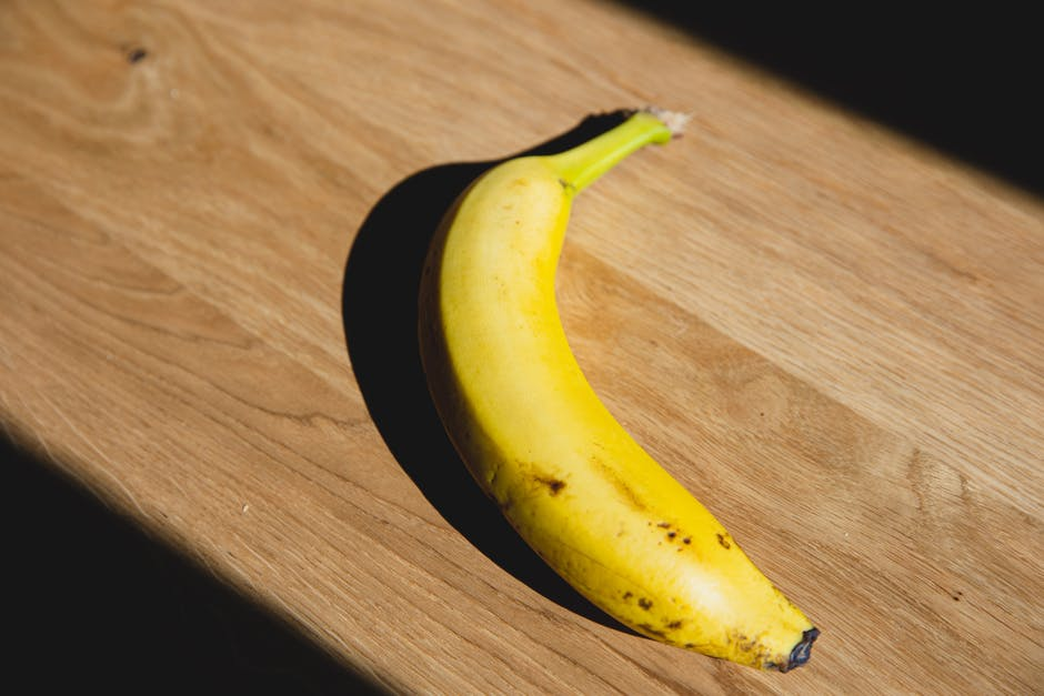 A banana sitting on top of a wooden cutting board