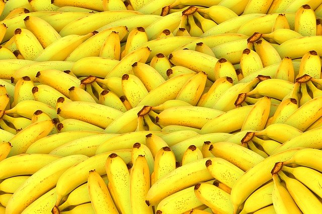 A pile of fruit sitting next to a banana