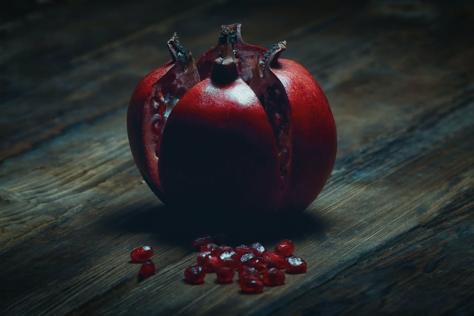 An pomegranate sitting on top of a wooden table