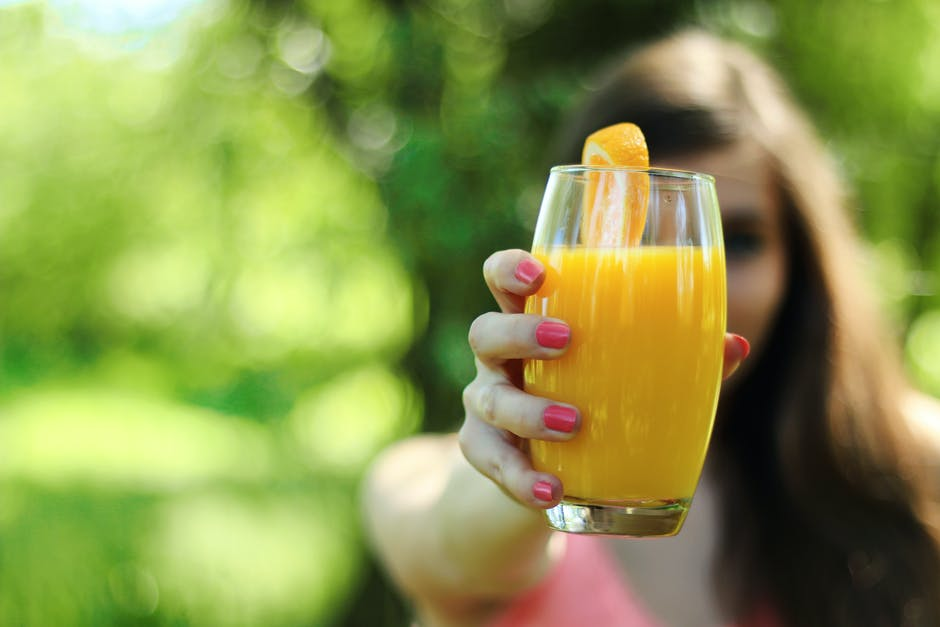 A hand holding a glass of orange juice