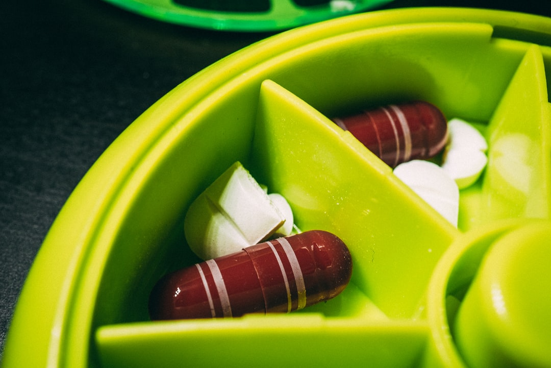 A plastic container with a green bowl filled with fruit