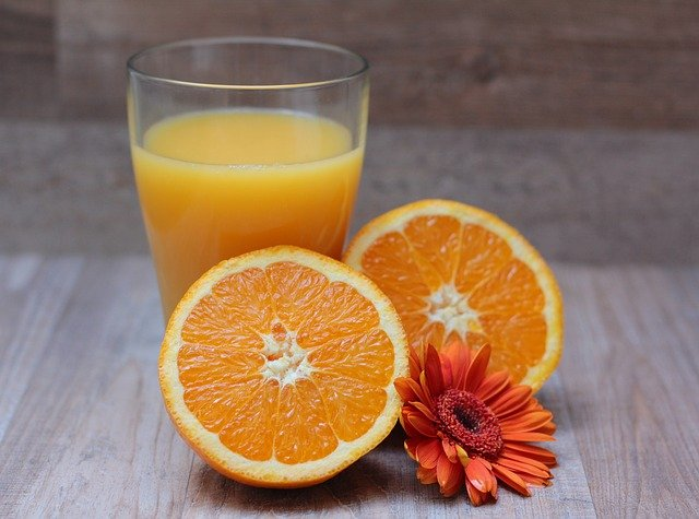 Two oranges and a glass of orange juice
